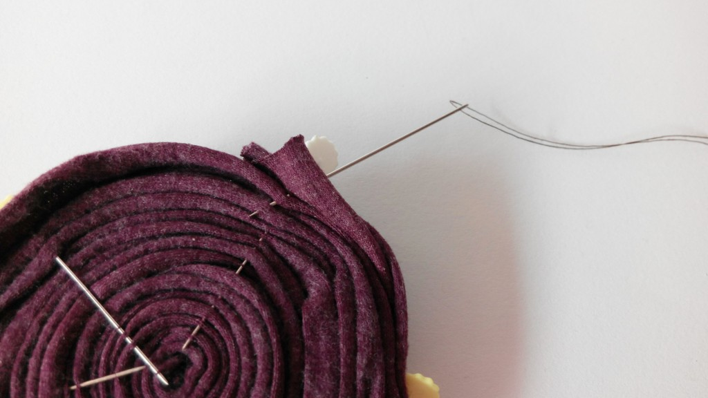 Cose la parte trasera del broche tratando de unir las tiras de trapillo