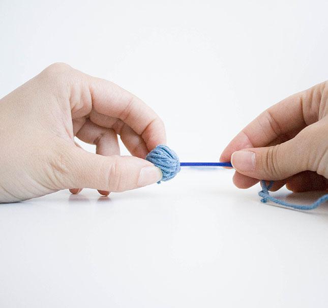 Con ayuda de la aguja metemos la hebra por el ovillo